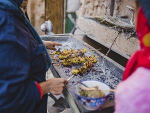 Street cooking skewers over coals
